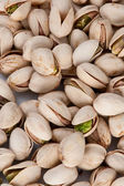 A background of pistachio nuts on a white table — Stock fotografie