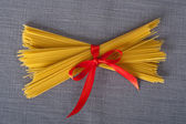 Bunch of spaghetti with a red ribbon on a table cloth ready to be cooked in an italian recipe — Stock Photo