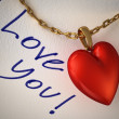 Stock Photo: Red shiny heart pendant, with gold chain, on a white paper and t