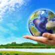 Stock Photo: Mhand with earth globe on it and beautiful green landscape