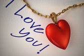 Ciondolo cuore rosso lucido, con catena d'oro, su una carta bianca e t — Foto Stock