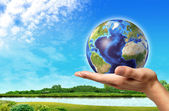 Man hand with earth globe on it and a beautiful green landscape — Stock Photo