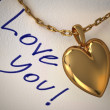 Gold heart pendant on a white paper with the type I love you, ha — Stock Photo