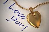 Gouden hart hanger aan een witboek met het type dat ik hou van je, ha — Stockfoto