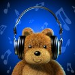 Teddy bear with music headphones. Blue background and musical notes. — Stock Photo