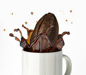 Giant Coffee bean splashing in mug. Close up view. — Stock Photo