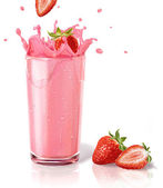 Strawberries splashing into a milkshake glass, with two others o — Stock Photo