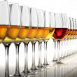 Stock Photo: Row of many white wine glasses, with a red one standing out in t
