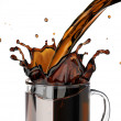 Pouring coffee splashing into a glass mug. — Stock Photo