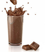 Chocolate cubes splashing into a choco milkshake glass. With two — Stock Photo