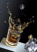 Cubo di ghiaccio spruzzi in un bicchiere di liquido. — Foto Stock