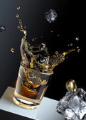 Ice cube splashing into a glas of liquid. — Stock Photo