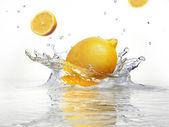 澄んだ水にしぶきのレモン — ストック写真