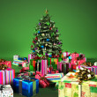 Christmass tree with several gifts, in a green background. — Stock Photo