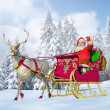 Santa Claus on his sleigh and reindeer on snow, with snow capped - Stock Photo