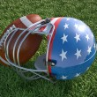 American football helmet and ball, on the grass. Close up. — Stock Photo #29916523