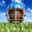 American football helmet over the oval ball, on the grass. Front — Stock Photo