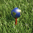 Golf ball on tee in the grass, with earth planet map. — Stock Photo