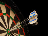Dartboard with three darts in center target. — Stock Photo