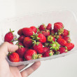 Male take in hand plastic dish with red strawberry — Stock Photo