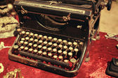 Retro typewriter on a red tablecloth for sale at a flea market — Stock Photo