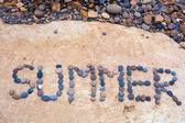 Inscription on a plate lined with small stones of summer sea — Stock Photo