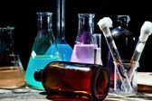 Volumetric laboratory glassware containing colored liquids — Stock Photo