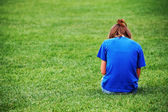 Young girl sitting on the grass — Stock Photo