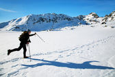 Alpinist traversing an iced lake in National Park Retezat, Romania — Stock Photo