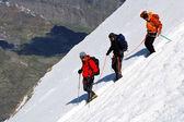 从这里登山降序冰冷的斜坡的团队 — 图库照片