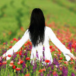 Young brunette beautiful girl enjoying the spring flowers — Stock Photo #29697567