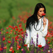 Young brunette beautiful girl enjoying the spring flowers — Stock Photo #29697581