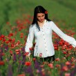 Young brunette beautiful girl enjoying the spring flowers — Stock Photo