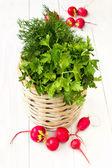 A bunch of fresh vegetables in a bowl wicker basket on white woo — 图库照片
