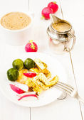 Farmer fresh breakfast with fried eggs, coffee, brussels sprouts and vegetables on a plate on white wooden background — Стоковое фото