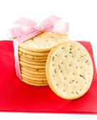 Festive Christmas shortbread wrapped pastry cookies with red ribbon — Stock Photo