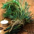 Bunch of fir tree or pine branches and glowing candle on dark old background.  — Stock Photo