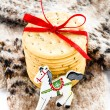 Christmas cookies with red ribbon and celebration wooden  horse  on knitted mitten and white background. — Stock Photo