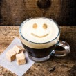 Small cup of espresso coffee in glass with smile pattern on old wooden table. — Stock Photo