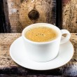 Closeup cup of espresso on old wooden table over grunge background — Stock Photo #29602217