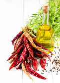 Olive oil bottle, herbs and vegetables on white background — Stock Photo