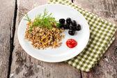 Buckwheat porridge, black olives and herbs on white plate on rustic dark wooden board. — Stock Photo