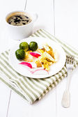 Fresh breakfast with fried eggs, brussels sprouts and radish on a plate on white background. — Stock Photo
