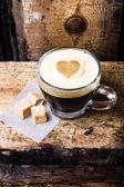 Small cup of espresso coffee in glass with heart drawning on foam — Stock Photo