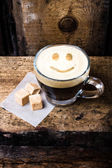 Cappuccino coffee with smile drawing art foam in glass small cup. — Stock Photo