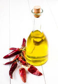 Olive oil bottle and Red hot chili pepper on white wooden background. — ストック写真