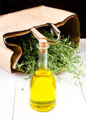 Olive oil bottle and herbs with paper bag on white wooden background. — ストック写真