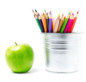 Color pencils in tin can or pencil holders and green apple — Stock Photo
