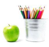 Färgpennor i plåtburk eller pencil innehavare och grönt äpple — Stockfoto