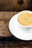 Closeup cup of espresso on old wooden table over grunge background — Stock Photo